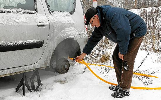 мужчина отогревает тормоза выхлопными газами