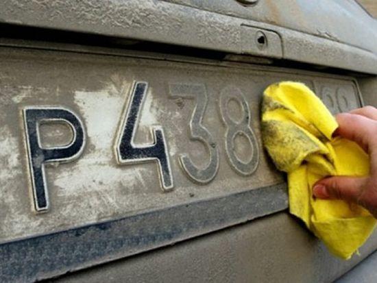 водитель протирает грязный номер на автомобиле