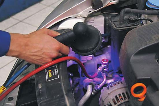 механик ищет утечку фрелна под капотом авто
